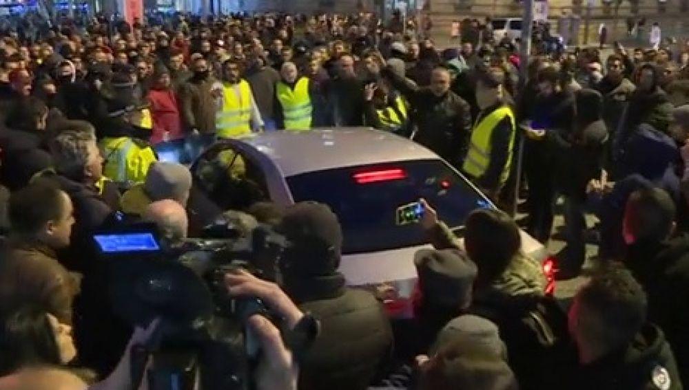 Taxistas cercando a un vehículo VTC