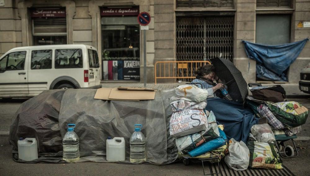 Una mujer con sus pertenencias en un banco de Madrid