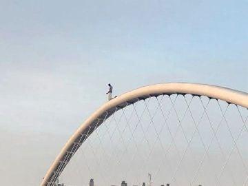 El hombre encaramado a lo alto de la pasarela