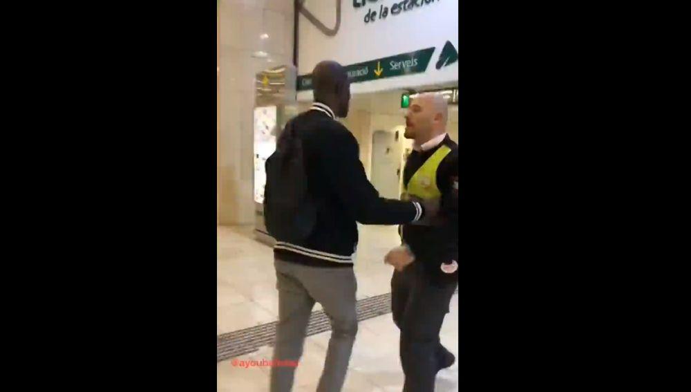 Un guardia de seguridad impide el paso de un hombre de color en la Estación de Sants