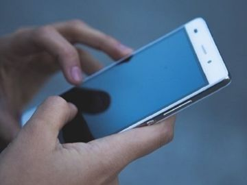 Imagen de archivo de una persona con un teléfono móvil en la mano