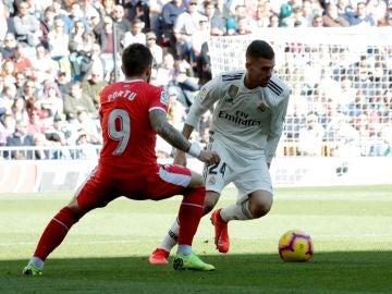 Dani Ceballos intenta controlar el balón ante el centrocampista del Girona, Portu