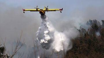 Un hidroavión durante las tareas de extinción de un incendio declarado en los montes próximos a la localidad cántabra de Penilla