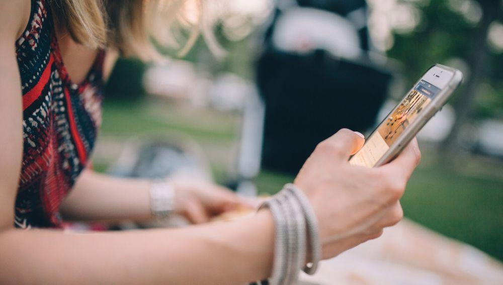 Chica usando un móvil (Archivo)