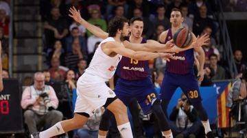 Llull intenta pasar el balón ante la defensa de los jugadores del Barcelona