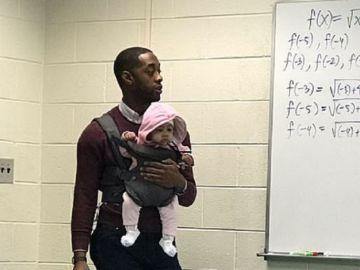 Imagen de un profesor con una bebé en brazos mientras daba clase