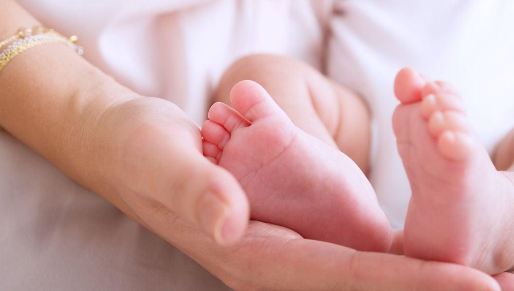 Una madre sosteniendo los pies de su bebé