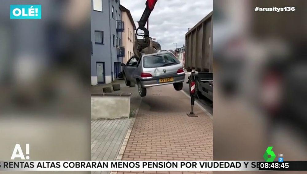 El trabajador de un desguace utiliza una de sus grúas para retirar un coche aparcado en la puerta de su garaje