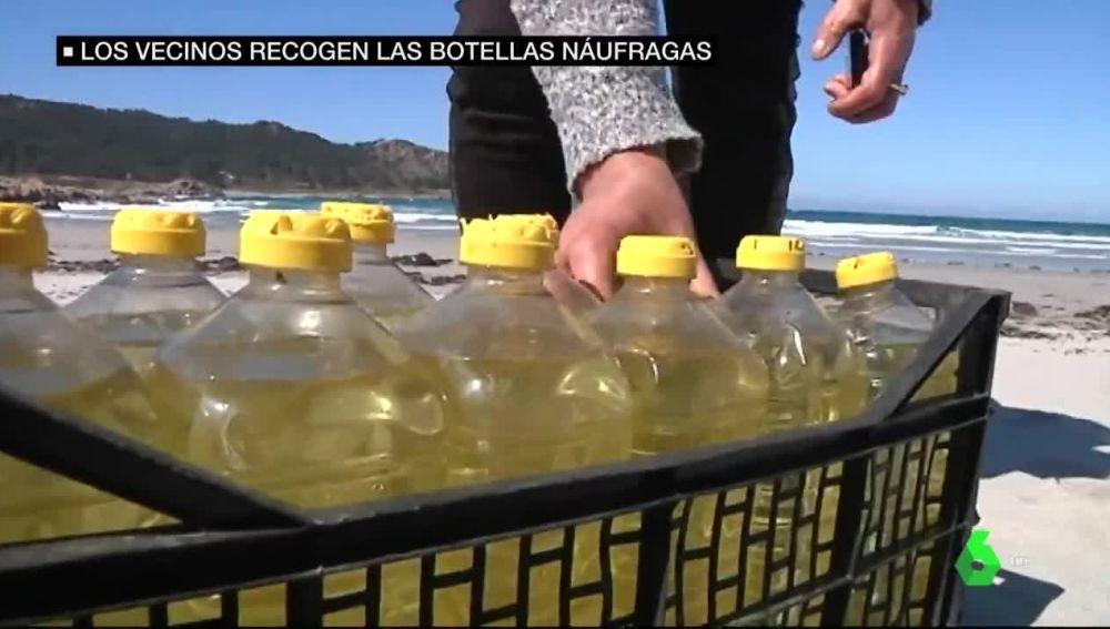 Una caja con botellas de aceite en la playa de Camariñas, A Coruña