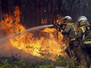 Los bomberos apagan un fuego en Rianxo, Galicia.