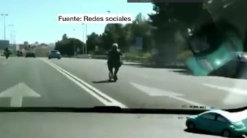 Una mujer conduce un patinete por la autovía de Valencia