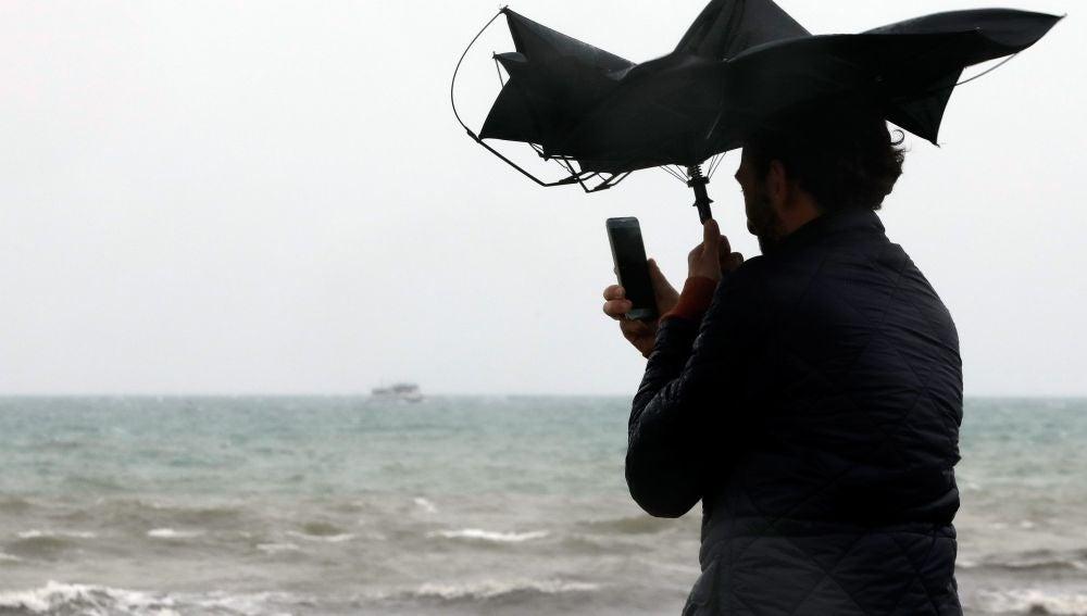 Una persona en la Playa de la Malvarrosa de Valéncia bajo la lluvia y el fuerte viento.