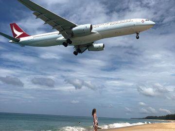 Imagen de una mujer junto a un avión en la playa a la que se ha prohibido el acceso