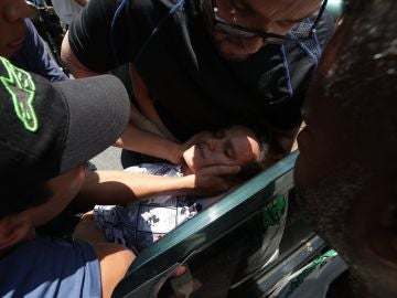 Simpatizantes de Guaidó ayudan a una mujer herida por una bala en el estómago