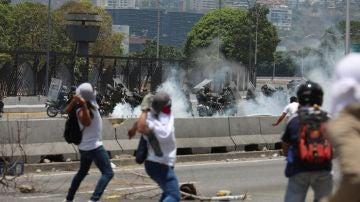Manifestantes opositores se enfrentan con miembros de la Guardia Nacional Bolivariana en las calles de Caracas (Venezuela) este miércoles, un día después del efímero levantamiento militar encabezado por Juan Guaidó.