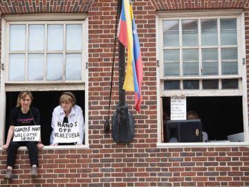 Acivistas con carteles contra Juan Guaidó en la embajada de Venezuela en Washington