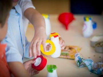 Dos niños pequeños fabrican juguetes con materiales reciclados.