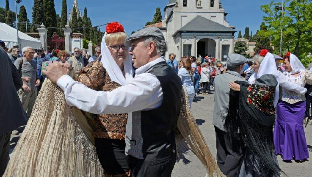 Varias personas bailan chotis en las celebraciones de San Isidro.