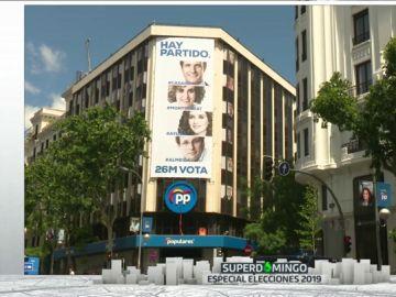 Una nueva lona con la foto de los candidatos cubre la fachada del PP en Génova