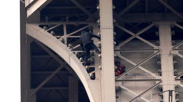 Un hombre escala la Torre Eiffel mientras varios bomberos tratan de detenerlo