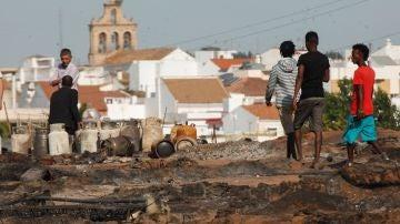 Varias personas caminan por lo que queda del asentamiento chabolista