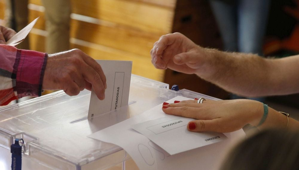 Imagen de archivo de un votante depositando su papeleta en las urnas.