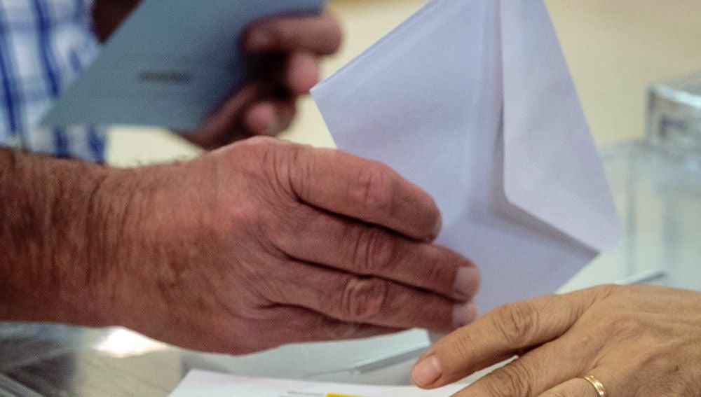 Una ciudadana deposita su voto en la urna en un colegio electoral