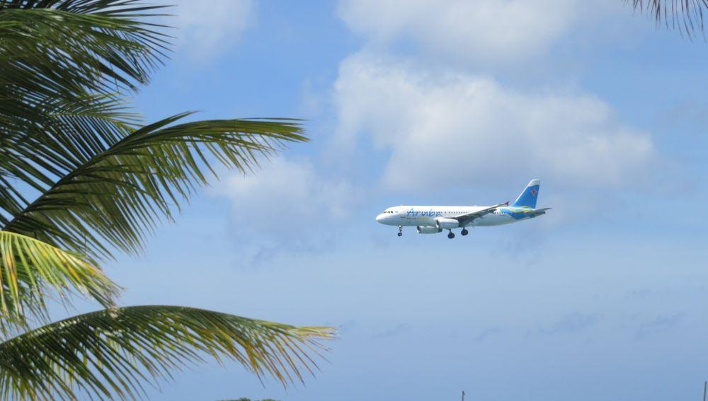 Imagen de un avión volando cerca de una playa.