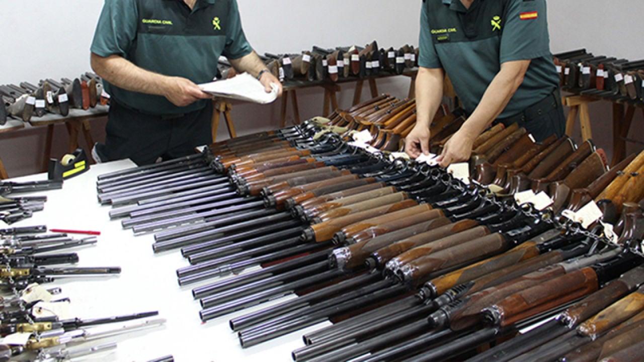 Dos agentes de la Guardia Civil revisan numerosas escopetas y armas