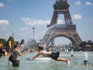 Una mujer se refresca con el agua de la fuente de la Plaza del Trocadero