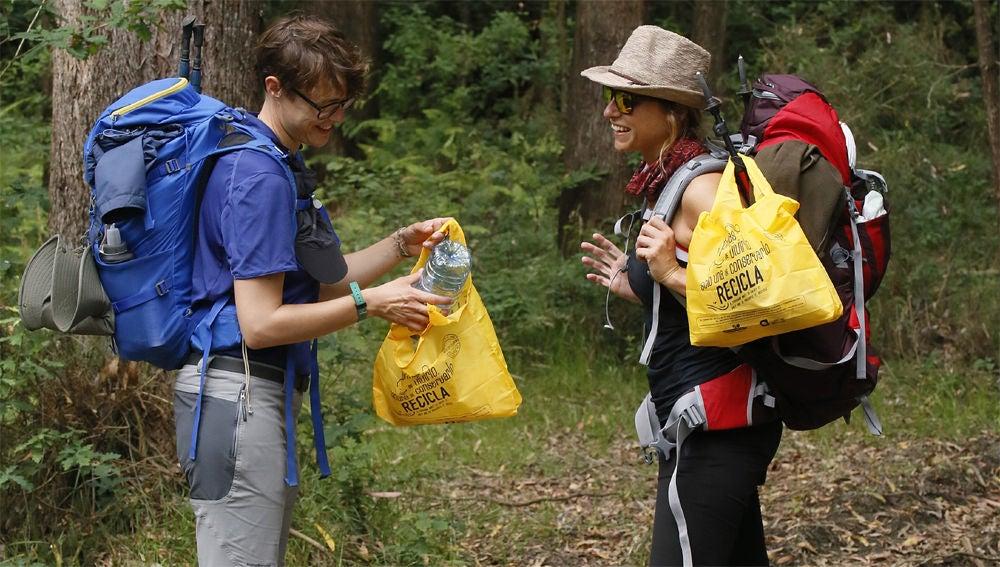 Peregrinos del Camino de Santiago separando envases para su reciclaje.