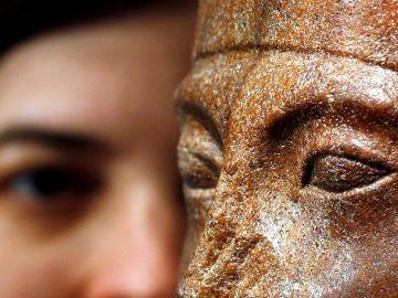 La jefa de antiguedades de Christie's posa junto a una cabeza de cuarcita marrón del joven rey Tutankamón.
