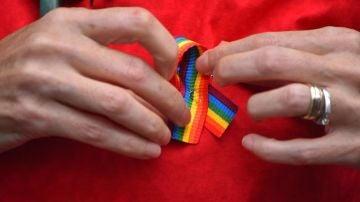 Una persona poniéndose un lazo LGTBI