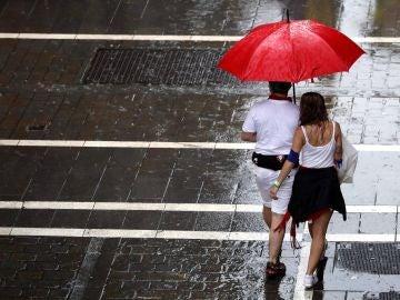 Dos personas se protegen de la lluvia en una de las céntricas calles de Pamplona