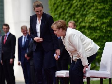 Merkel participa sentada en los honores militares para evitar un nuevo temblor.