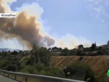 Una veintena de medios terrestres y aéreos trabajan en la extinción de un incendio en Robregordo, Madrid