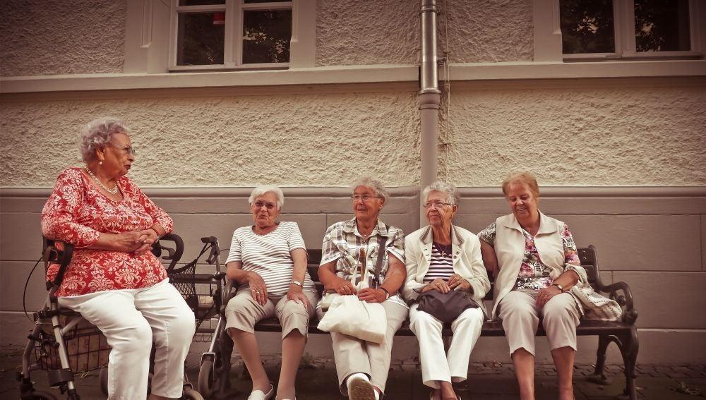 mujeres jubiladas hablando en un banco