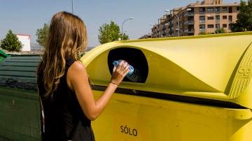 Una mujer deposita una botella de plástico en un contenedor amarillo.