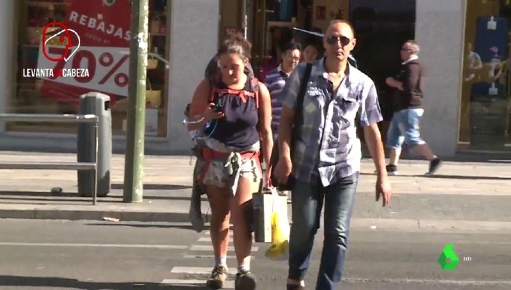 Una mujer utilizando su teléfono móvil en un paso de peatones.