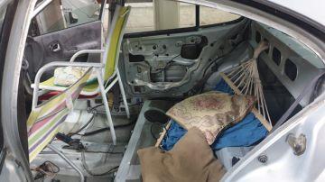 Interior de un vehículo que lleva sillas de playa y una hamaca en lugar de asientos