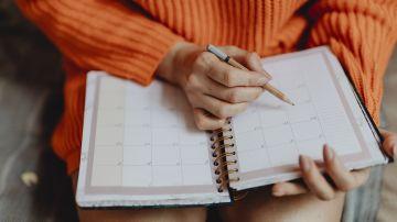Imagen de archivo de una chica apuntando notas en el calendario de una agenda.