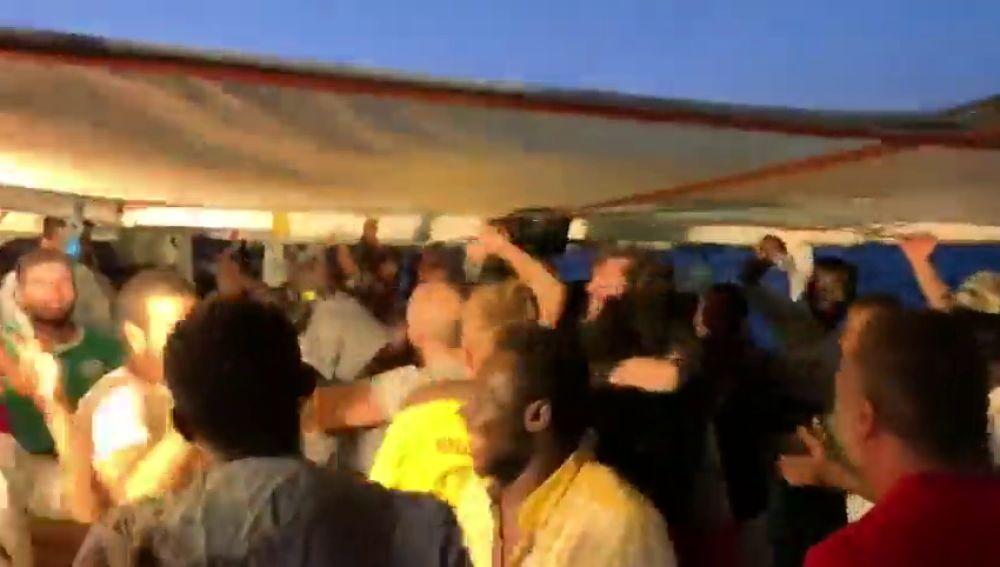 Abrazos, sonrisas y gritos de alegría en el Open Arms tras enterarse de que los migrantes desembarcarán en Lampedusa