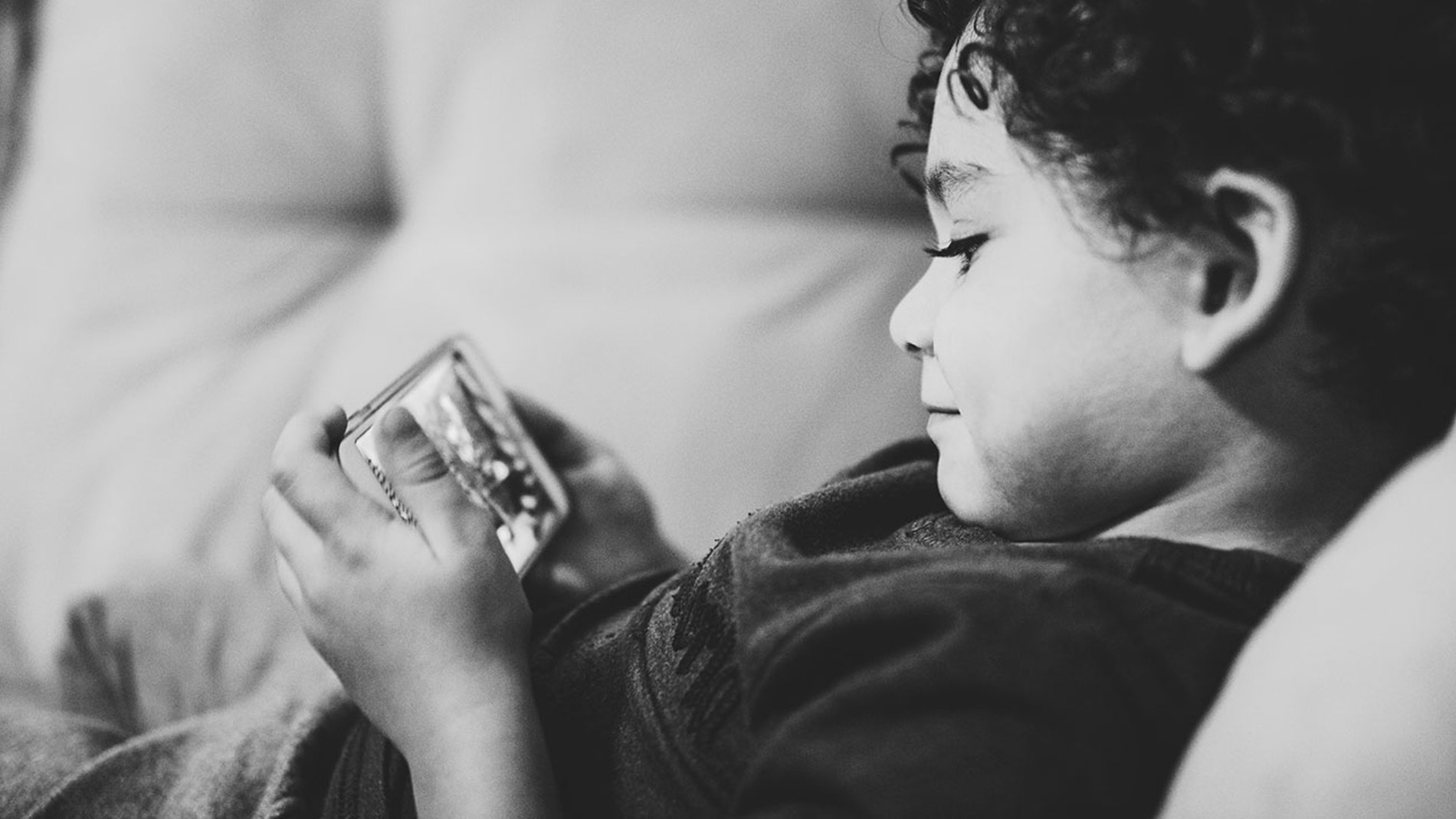 Un niño con un móvil en las manos