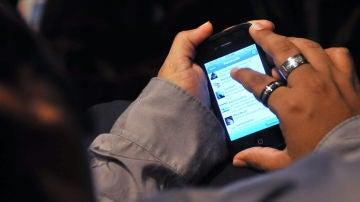 Un joven revisa su teléfono móvil