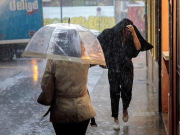 Does personas caminan bajo la lluvia intensa en Valencia