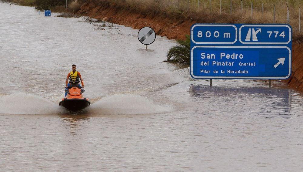 Un miembro de los servicios de rescate cruza en moto acuática la salida del túnel de la AP-7 en Pilar de la Horadada
