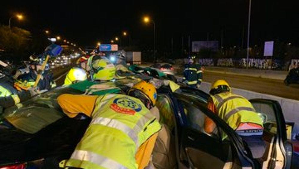 Bomberos trabajando en el rescate de uno de los implicados en el accidente