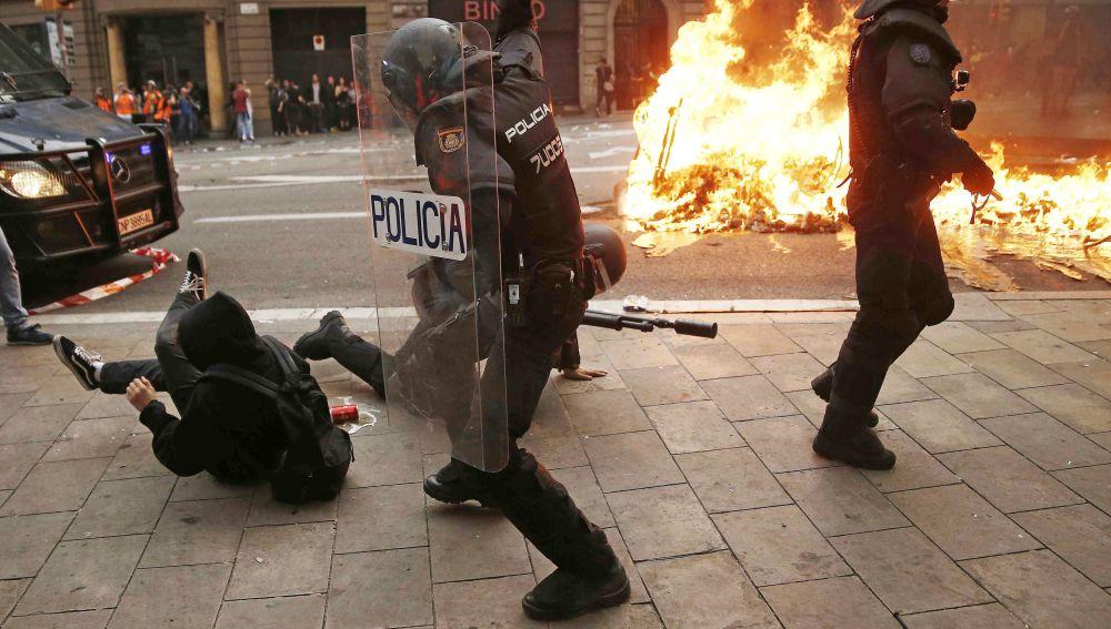 Policías antidisturbios y manifestantes durante los incidentes en Barcelona