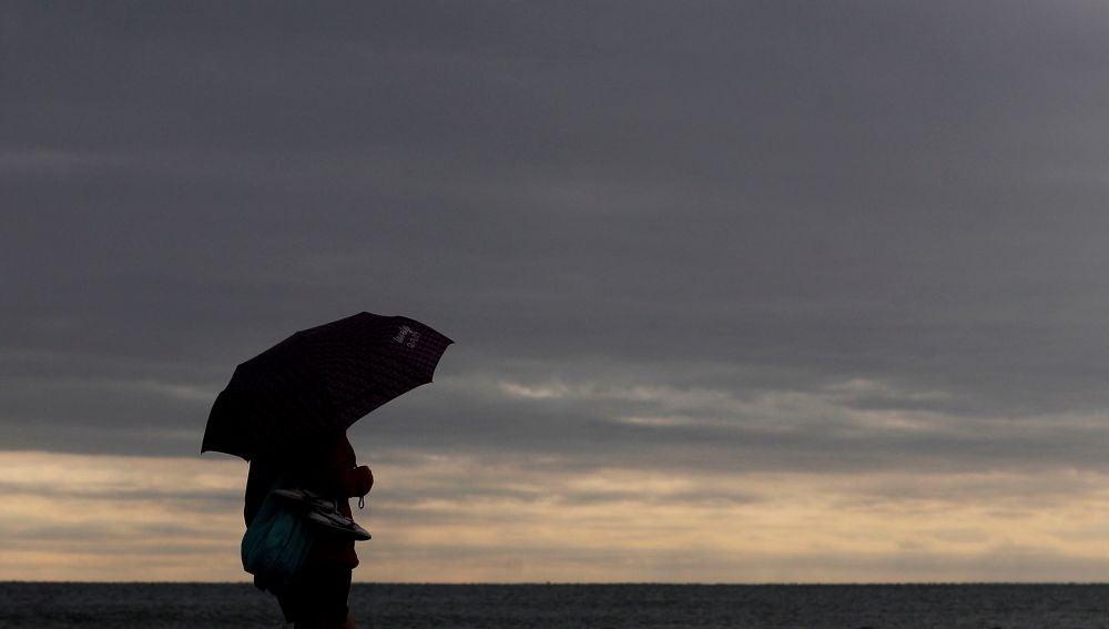 Una persona pasea por la playa de la Malvarrosa protegida con un paraguas
