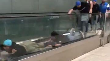 """Aficionados del Atalanta """"nadando"""" sobre la cinta mecánica de un aeropuerto"""